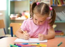 La petite fille mignonne dessine avec le crayon lecteur feutre images stock