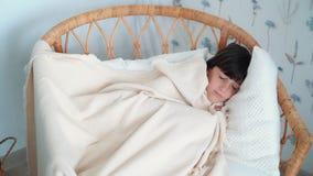 La petite fille mignonne dort tranquillement dans la chaise, prend la couverture pendant les rêves, mouvement lent banque de vidéos