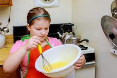 La petite fille mignonne douce apprend comment faire un gâteau, dans les kitchenlearns à la maison pour faire cuire un repas dans photographie stock