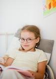 La petite fille mignonne en verres s'assied dans le lit et garde le livre sur son recouvrement photographie stock libre de droits