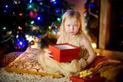 La petite fille mignonne est peu satisfaite de son cadeau de Noël Photos stock