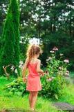 La petite fille mignonne est se tenante et rêvante au jardin dans chaud Photo stock