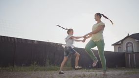 La petite fille mignonne et sa mère tournant tenir autour des mains dans l'arrière-cour La femme et l'enfant ayant l'amusement de banque de vidéos
