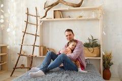 La petite fille mignonne et son père beau s'asseyent sur le divan à la maison Image libre de droits