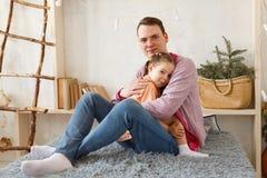 La petite fille mignonne et son père beau s'asseyent sur le divan à la maison Photographie stock