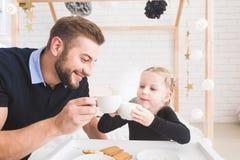 La petite fille mignonne et son père boivent du thé avec des biscuits à la maison images libres de droits