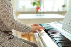 La petite fille mignonne a la formation avec le piano Photo stock