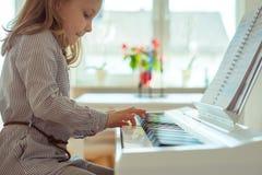 La petite fille mignonne a la formation avec le piano Image stock