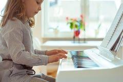 La petite fille mignonne a la formation avec le piano Images libres de droits