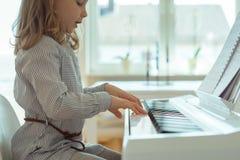 La petite fille mignonne a la formation avec le piano Photo libre de droits