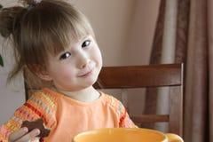 La petite fille mignonne mange des biscuits Image stock