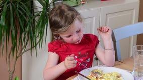 La petite fille mignonne mange le dîner La fille de Litlle mange dans la cuisine Fille dans la cuisine 4K banque de vidéos