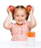 La petite fille mignonne mange le raccord en caoutchouc et les pommes image libre de droits