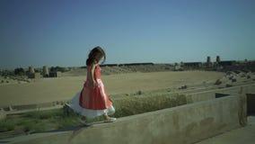 La petite fille mignonne marche sur le mur dans le grand amphithéâtre L'enfant ont un rêve L'enfant saute de la barrière La robe  clips vidéos