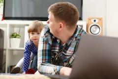 La petite fille mignonne observent sournoisement pour son papa Image stock