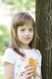 La petite fille mignonne a plaisir à manger son croissant préféré Images libres de droits