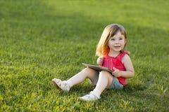 La petite fille mignonne s'assied avec un comprimé sur l'herbe en parc Verticale émotive Première éducation images stock
