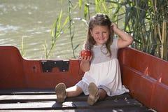 La petite petite fille mignonne s'assied dans un bateau sur un lac et tient AP Photo stock