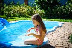 La petite fille mignonne s'assied sur la piscine Photos libres de droits