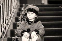 La petite fille mignonne s'est habillée dans le manteau de style rétro à l'intérieur de la vieille maison Photos libres de droits