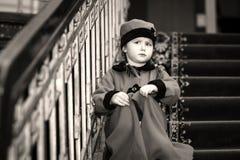 La petite fille mignonne s'est habillée dans le manteau de style rétro à l'intérieur de la vieille maison Image stock