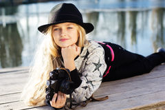 La petite fille mignonne se repose près du lac avec l'appareil-photo Photographie stock