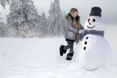La petite fille mignonne, se tenant sur la neige et fait un bonhomme de neige avec la neige La fille est habillée dans l'habillem photos libres de droits