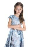 La petite fille mignonne se tient contre le blanc photo stock