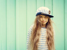 La petite fille mignonne se tient près d'un mur de turquoise dans le chapeau de marin et de l'espace de sourire pour le texte Photos stock
