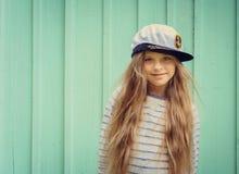 La petite fille mignonne se tient près d'un mur de turquoise dans le chapeau de marin et de l'espace de sourire pour le texte Image libre de droits