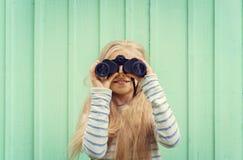 La petite fille mignonne se tient près d'un mur de turquoise et regarde des jumelles L'espace pour le texte Image stock