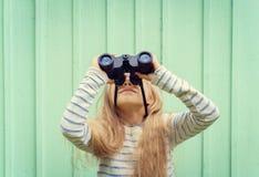 La petite fille mignonne se tient près d'un mur de turquoise et regarde des jumelles L'espace pour le texte Image libre de droits