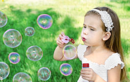 La petite fille mignonne souffle des bulles de savon Photos stock