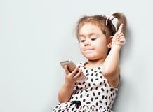 La petite fille mignonne tient le teleprone et les notes pour vider l'espace pour votre texte image stock