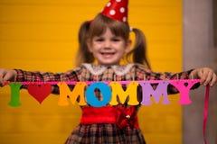 La petite fille mignonne tient une guirlande avec le ` de maman d'amour du ` I des textes de l'alphabet de papier coloré Images libres de droits