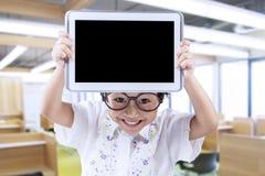 La petite fille moderne tient le comprimé dans la classe Image libre de droits