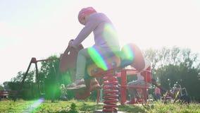 La petite fille monte le carrousel sur le terrain de jeu MOIS lent banque de vidéos