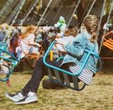 La petite fille monte un carrousel Photographie stock libre de droits