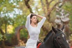 la petite fille monte un cheval Belle jeune femme dans une équitation blanche de robe sur un cheval brun dehors Photos stock