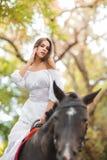 la petite fille monte un cheval Belle jeune femme dans une équitation blanche de robe sur un cheval brun dehors Photo libre de droits