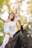 la petite fille monte un cheval Belle jeune femme dans une équitation blanche de robe sur un cheval brun dehors Photographie stock libre de droits