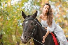 la petite fille monte un cheval Belle jeune femme dans une équitation blanche de robe sur un cheval brun dehors Images stock