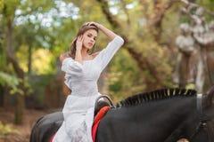 la petite fille monte un cheval Belle jeune femme dans une équitation blanche de robe sur un cheval brun dehors Images libres de droits
