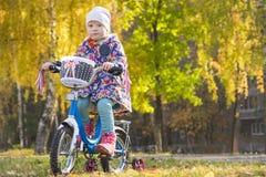La petite fille monte un vélo sur une pelouse d'automne Photographie stock