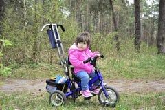 La petite fille monte une bicyclette dans les bois Images libres de droits