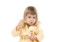 La petite fille nettoie des dents Photographie stock