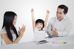 La petite fille obtiennent des applaudissements de ses parents photo stock