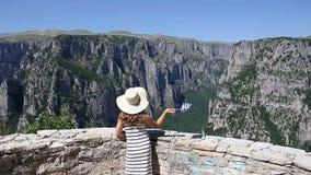 La petite fille ondule avec un drapeau grec sur la gorge de Vikos banque de vidéos