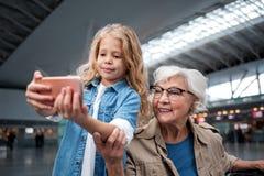 La petite-fille optimiste et sa mamie photographient dans le terminal Image stock