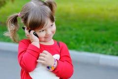La petite fille parle par le téléphone images libres de droits